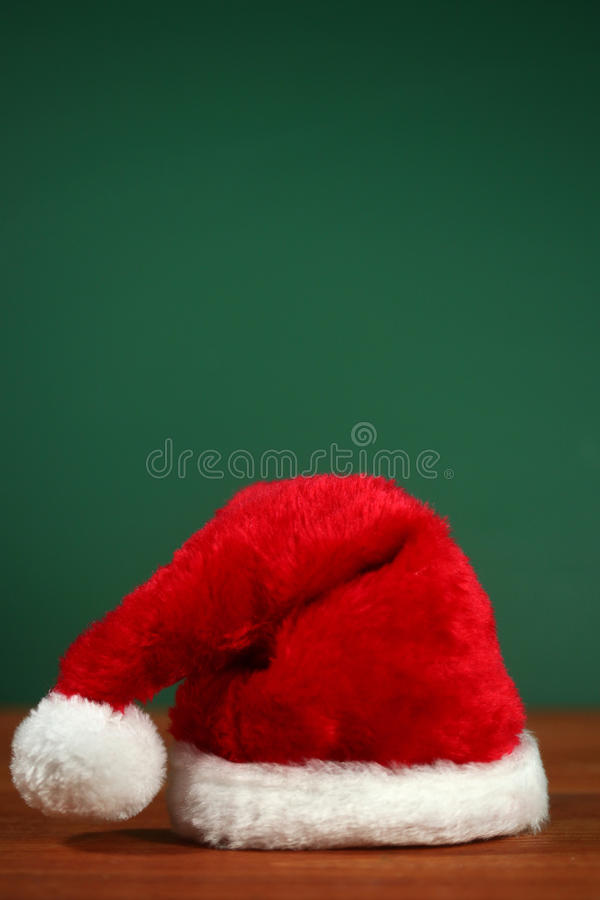 Red Santa Hat With Copy Space on Green and Wood Background royalty free stock photography