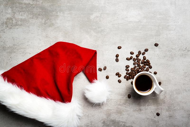 Red santa hat and a cup of coffee on a concrete table stock image