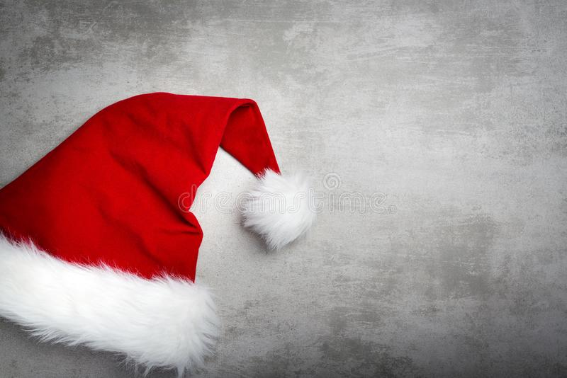 Red santa hat on a gray concrete table royalty free stock images