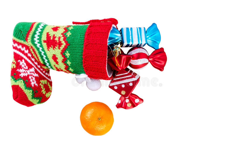 Red santa stocking with three decorative sweets inside and and m. Andarin. Isolated on white background. Top view stock photography