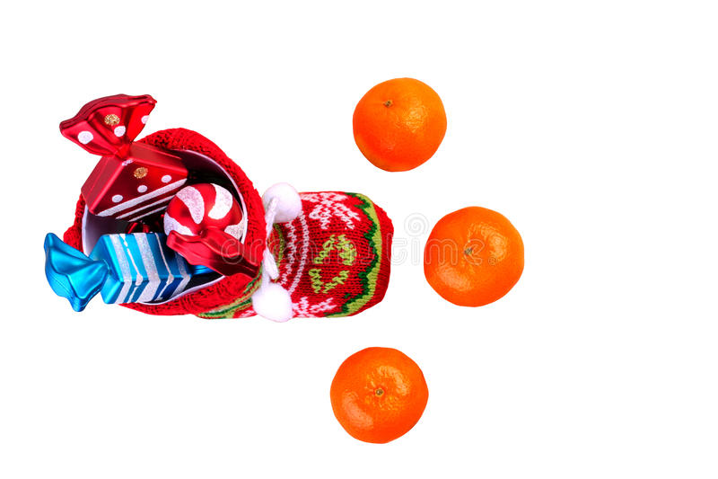 Red santa stocking with three decorative sweets inside and and t. Hree mandarins. Isolated on white background. Top view royalty free stock images