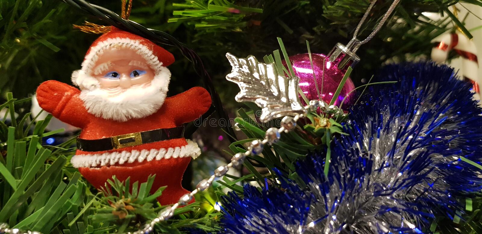 Red santa toy on Christmas tree royalty free stock image