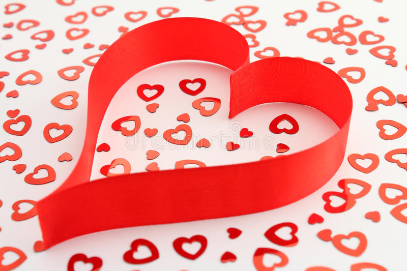 Red Satin Ribbon Heart With Heart-shaped Confetti Stock Images