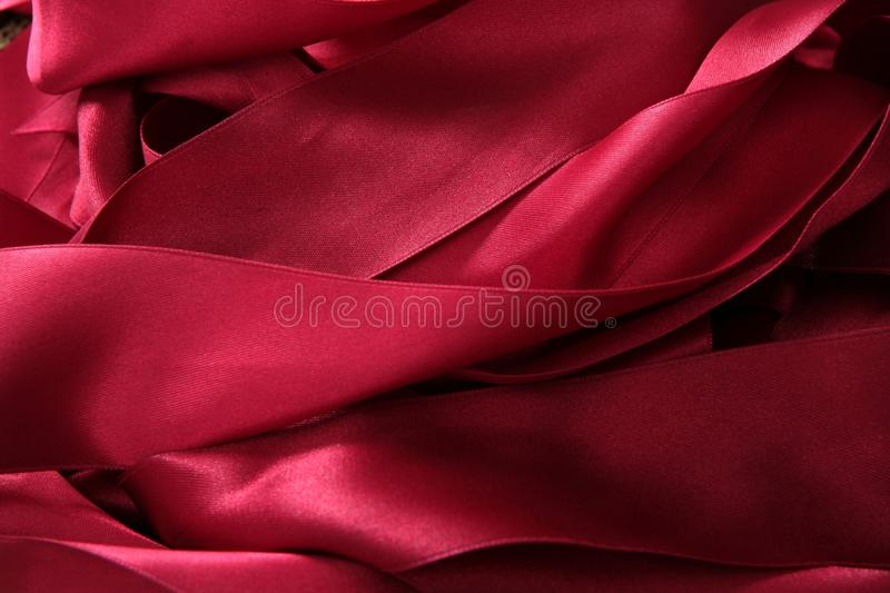 Red satin ribbons in a messy mess texture. Background royalty free stock photos