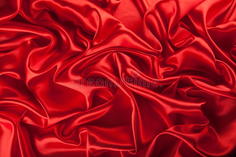 Red satin or silk fabric as background. Red satin silk fabric color expensive background stock photo