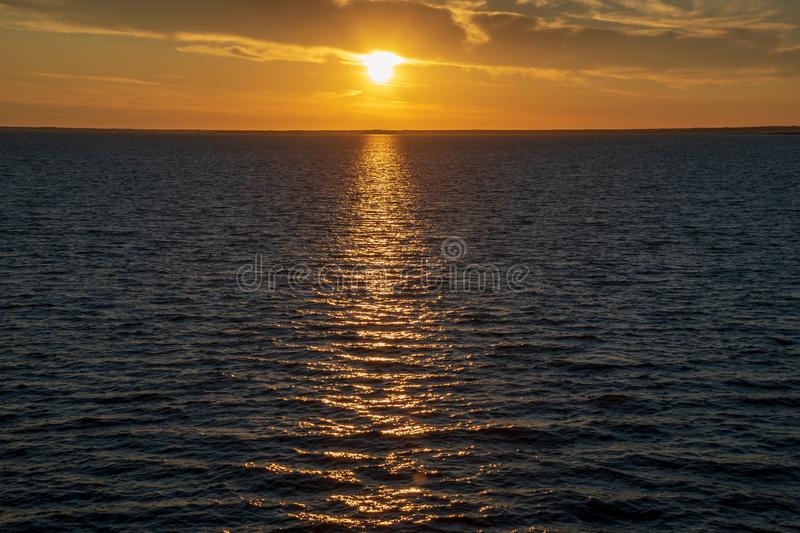 Red saturated colors in sunset over the baltic sea with calm water and sun reflections in Estonia stock images