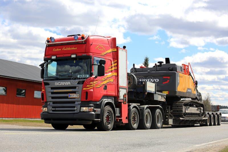 Red Scania Semi Trailer Hauls Hydraulic Excavator stock photo