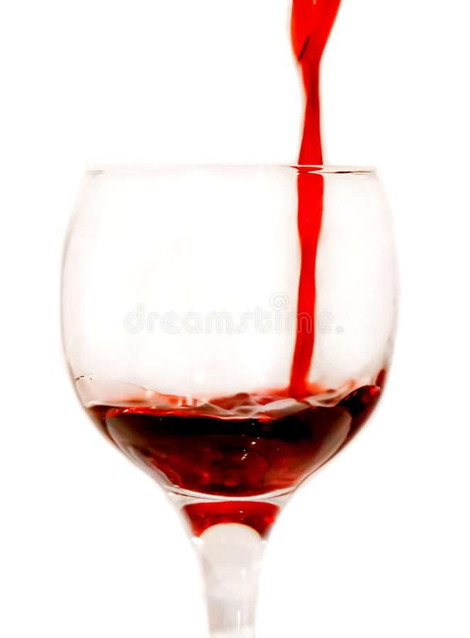 Red scarlet wine is poured into a glass. Beaker, large, isolate stock photo