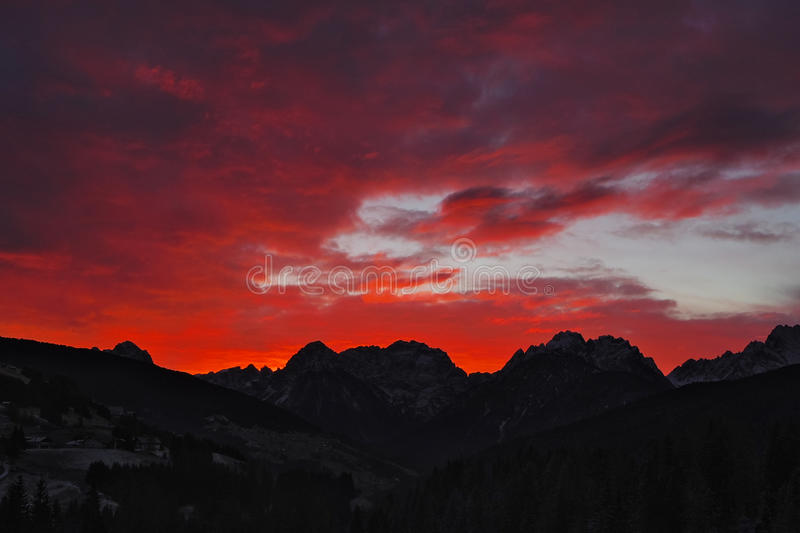 Red scenic sunset over the Dolomites of Comelico. Red scenic sunset over the Dolomites and villages of Comelico stock images