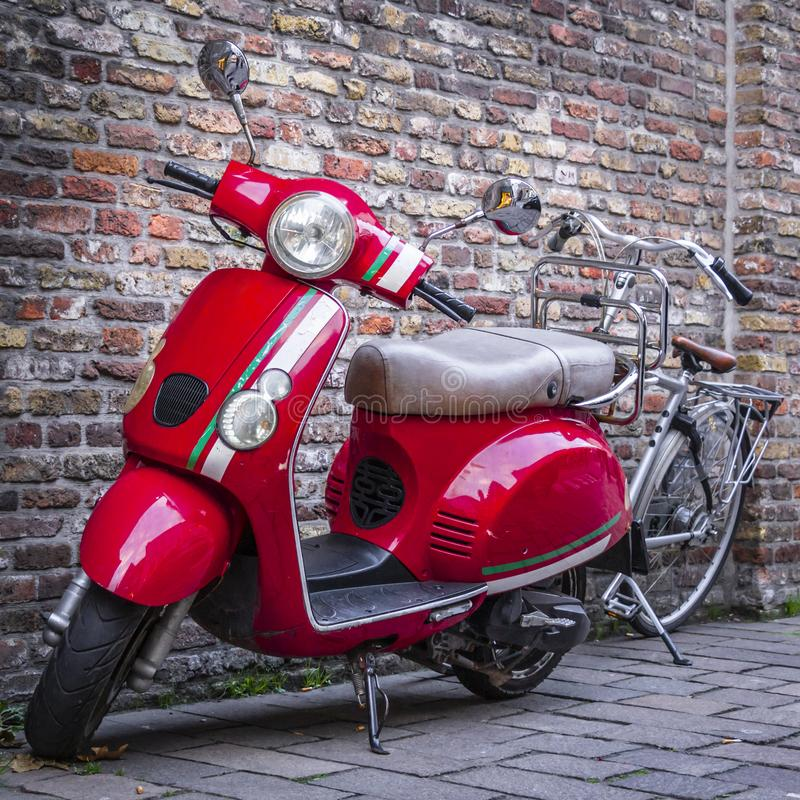 Red scooter and a silver bicycle near a vintage brick wall stock photo