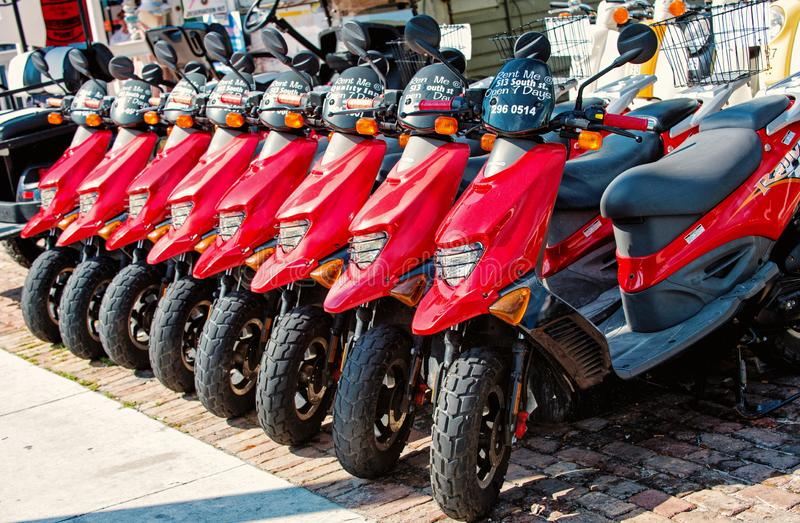 Red scooters, motorcycles for sale or hire, Key West, Florida. Key West, Florida - January 09, 2016: red scooters or motorcycles for sale or hire standing in row royalty free stock images