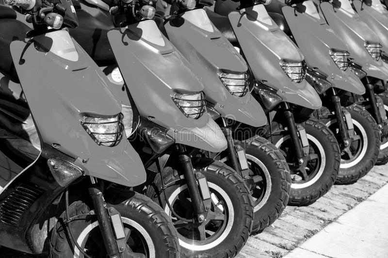 Red scooters or motorcycles for sale or hire in row. Red scooters or motorcycles for sale or hire standing in row with wheels and lights sunny day outdoor royalty free stock photos