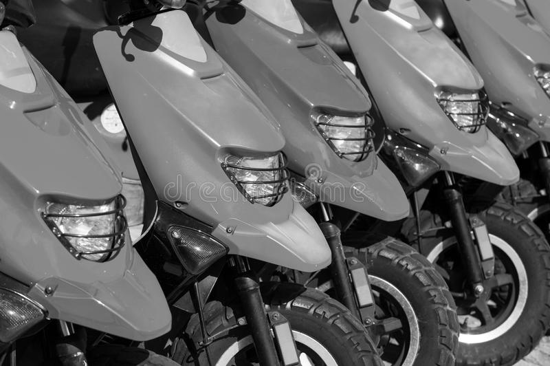 Red scooters or motorcycles for sale or hire in row. Red scooters or motorcycles for sale or hire standing in row with wheels and lights sunny day outdoor stock photo