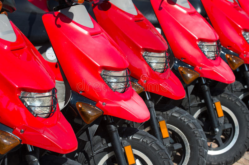 Red scooters or motorcycles for sale or hire in row. Red scooters or motorcycles for sale or hire standing in row with wheels and lights sunny day outdoor stock photography