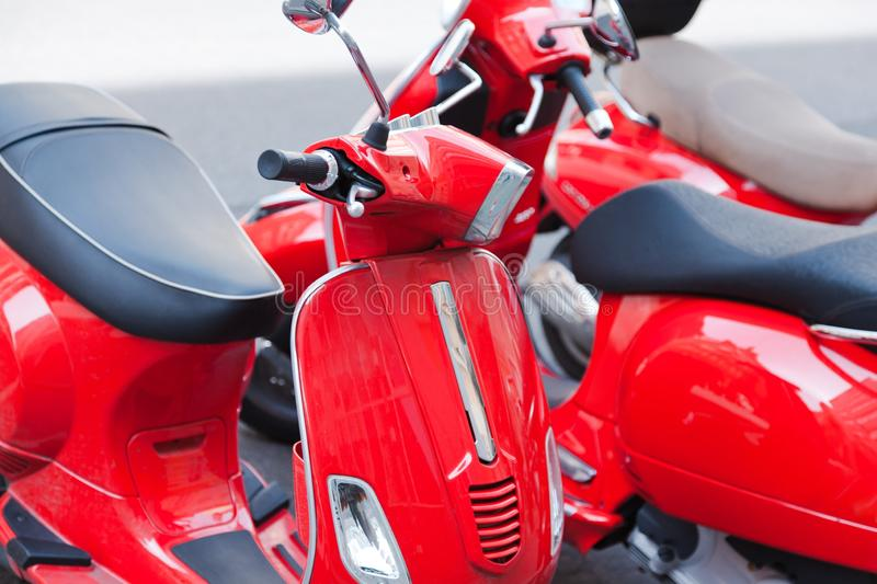 Red scooters parking on the streets. Close shots showing details of three bikes royalty free stock photo