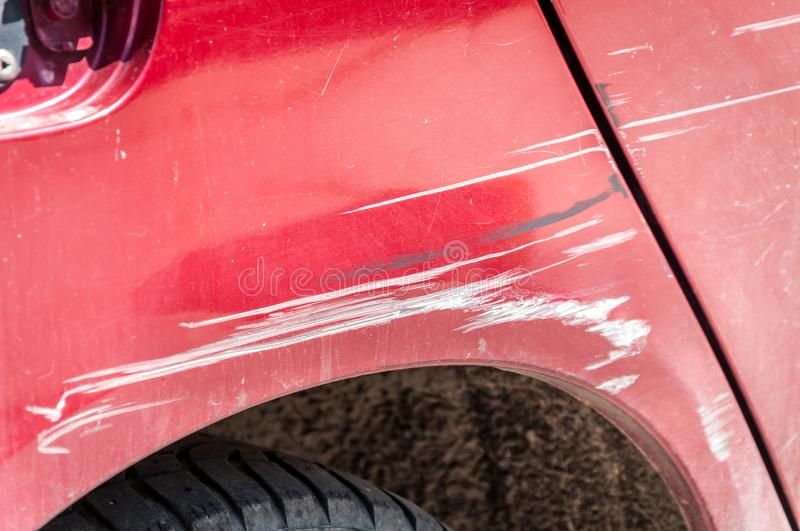 Red scratched car with damaged paint in crash accident on the street or parking lot in the city.  stock photos