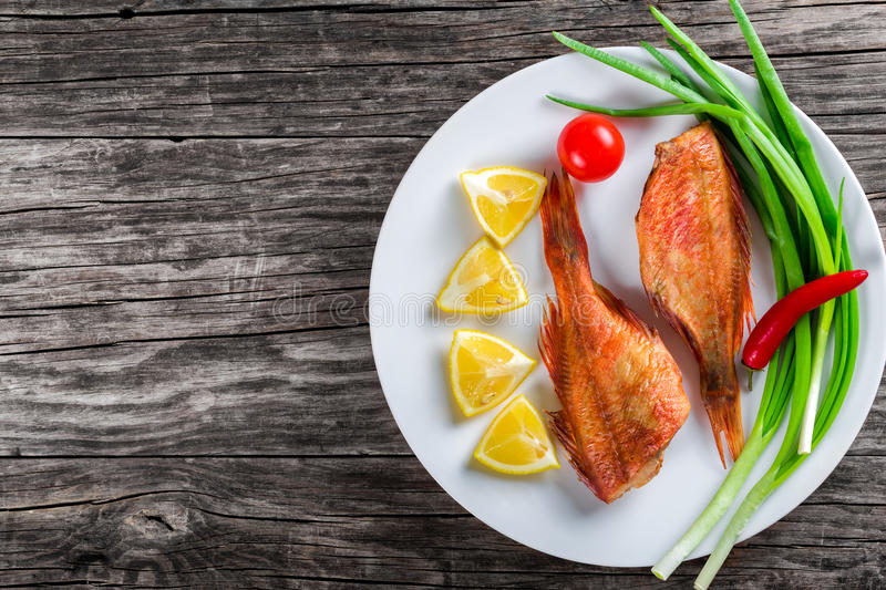 Red Sea Bass on white dish, top view. Red Sea Bass on a white dish with green spring onions, lemon slices and cherry tomato on an old wooden table, horizontal royalty free stock images