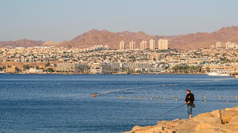 The Red sea, Eilat, fishing. One warm sunny morning on sea resort in a very quiet harbor with city and mountains at the background royalty free stock photography