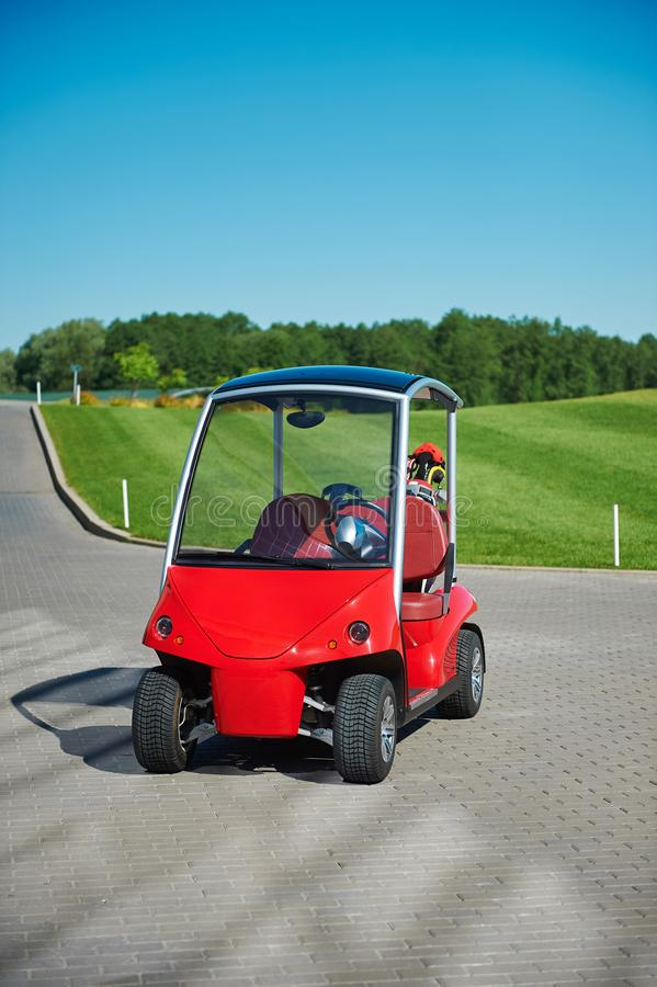 Red 2-seater golf electric cart on the paving road to a golf field royalty free stock photo
