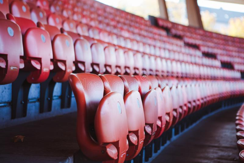 Red seats in unrecgonizable sports stadium. Empty red seats in sports stadium, unrecognizable location stock photography