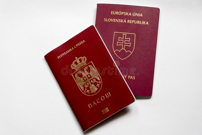 Serbian and Slovak passport on white background. Red Serbian passport and purple Slovak passport isolated on white background royalty free stock images