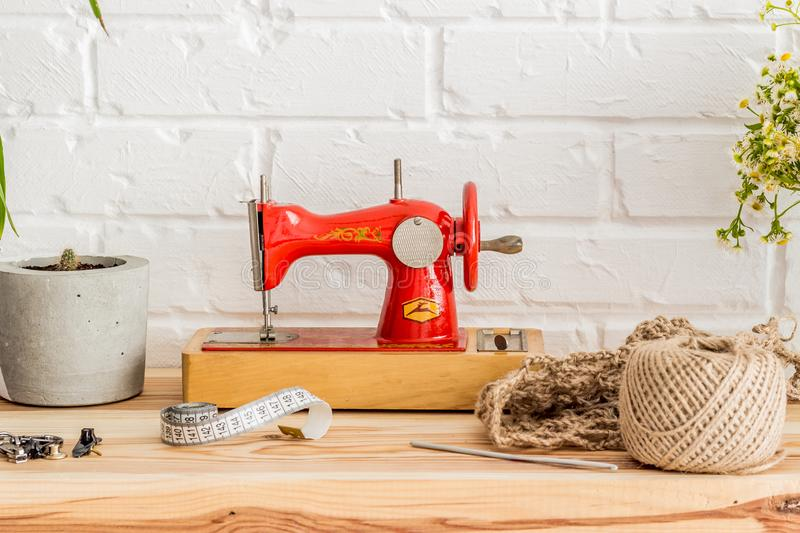Red sewing machine on a wooden table. Sewing industry. Diy stock photography