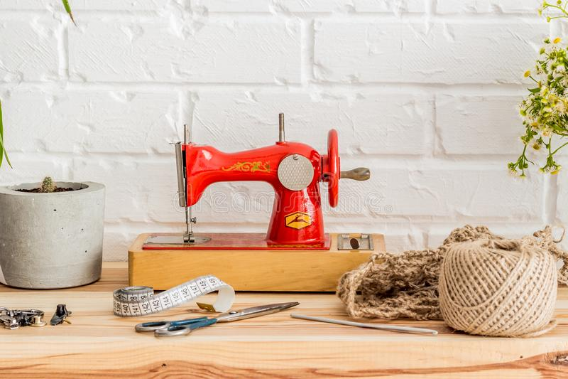 Red sewing machine on a wooden table. Sewing industry. Diy stock image