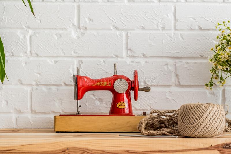 Red sewing machine on a wooden table. Sewing industry. Diy stock photo