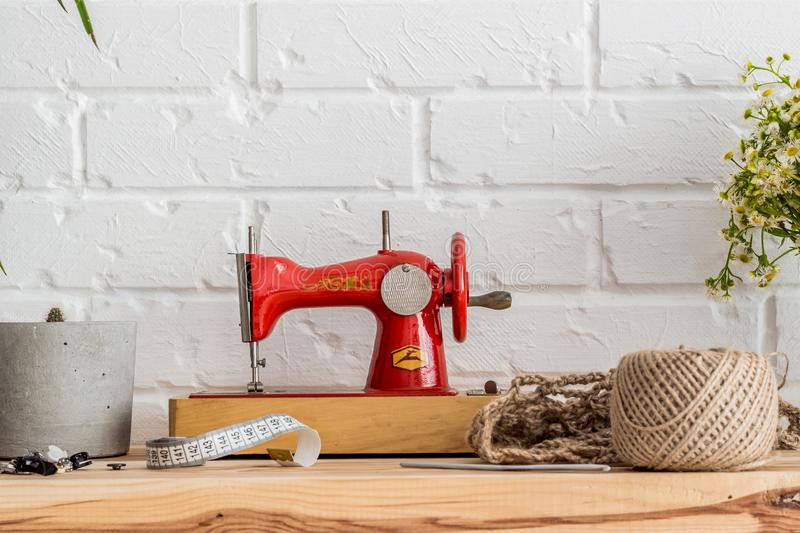 Red sewing machine on a wooden table. Sewing industry. Diy royalty free stock photography