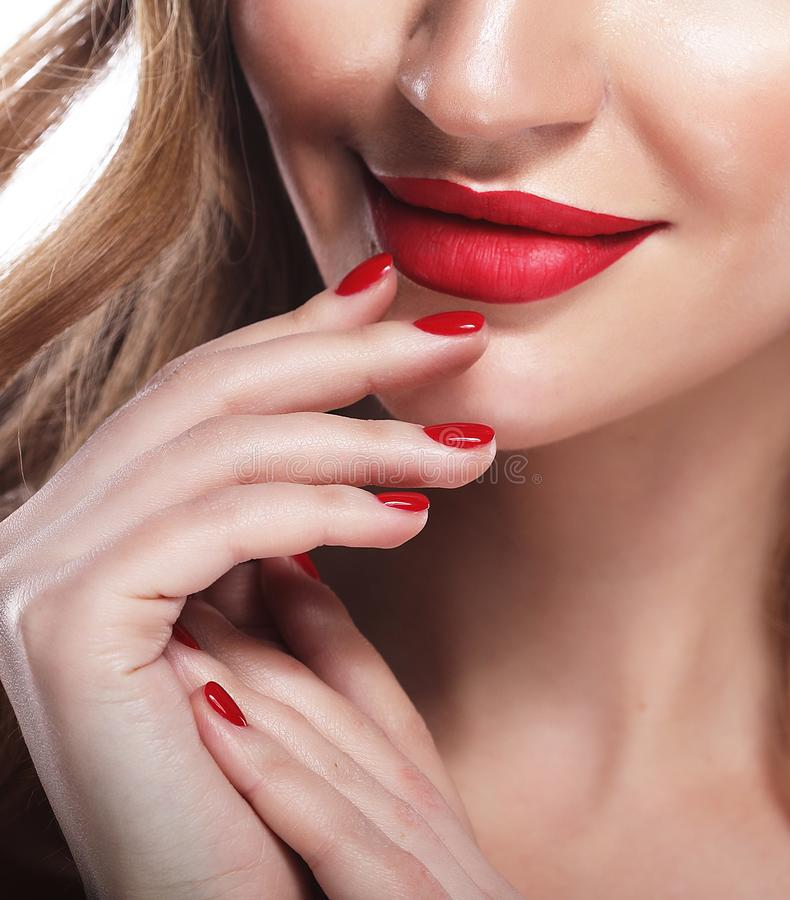 Red Lips and Nails closeup. Blond hair. Manicure and Makeup. Make up concept. Close up royalty free stock image