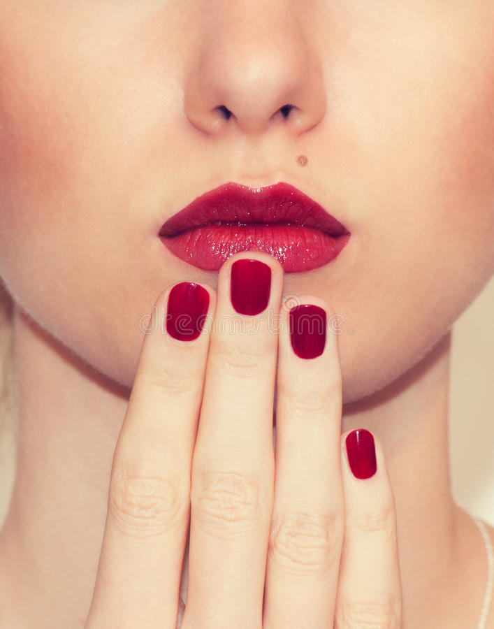 Red Lips and Nails closeup. Closed Mouth. Manicure and Makeup. Kiss stock image
