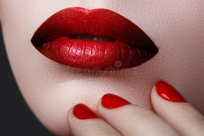 Red Lips and Nails closeup. Open Mouth. Manicure and Makeup. Make up concept. Beauty model girl's face on white background. Filler injections. Lip augmentation royalty free stock photos