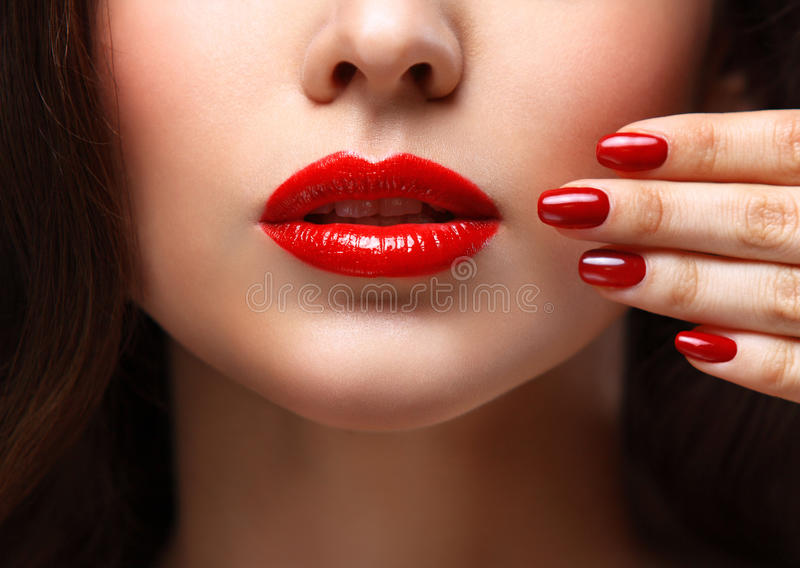 Red Lips and Nails closeup. Open Mouth. Manicure and Makeup. Make up concept. Half of Beauty model girl's face isolated on black stock image