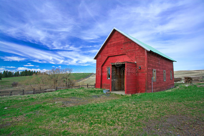 Red shed, green grass, blue sky.