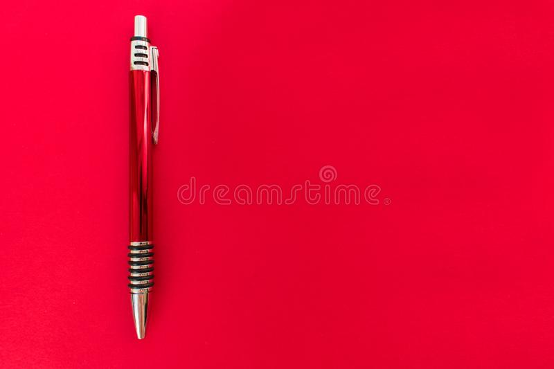 Red shiny ballpoint pen on red background. royalty free stock photography