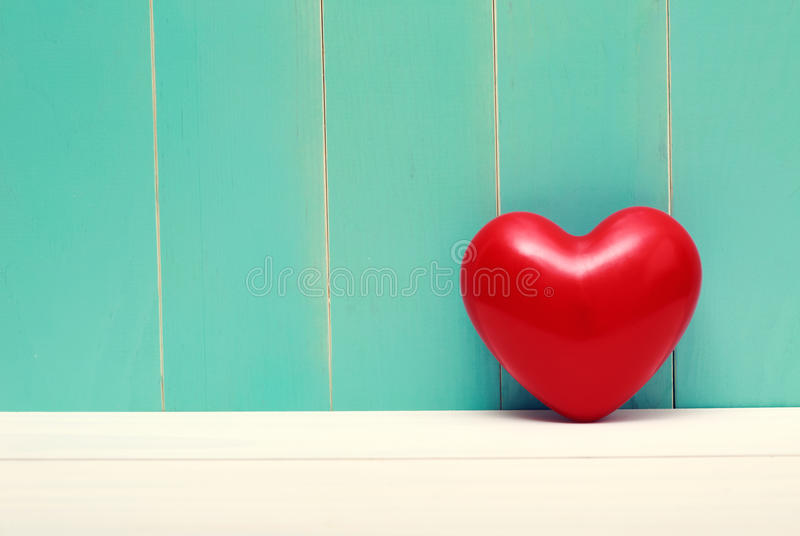 Red shiny heart on vintage teal wood royalty free stock images