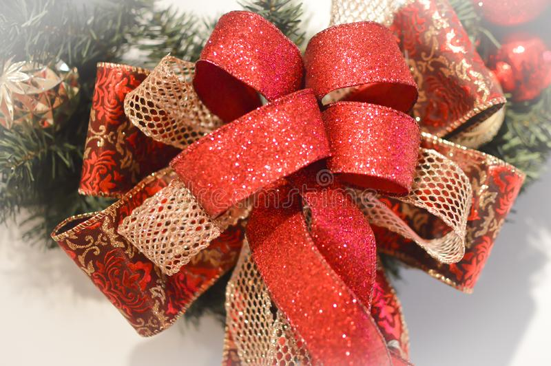 Red and Gold Christmas Bow. A red shiny ribbon with Gold mesh and a red and gold patterned ribbon forming a beautiful bow on the bottom of a holiday Christmas stock photos