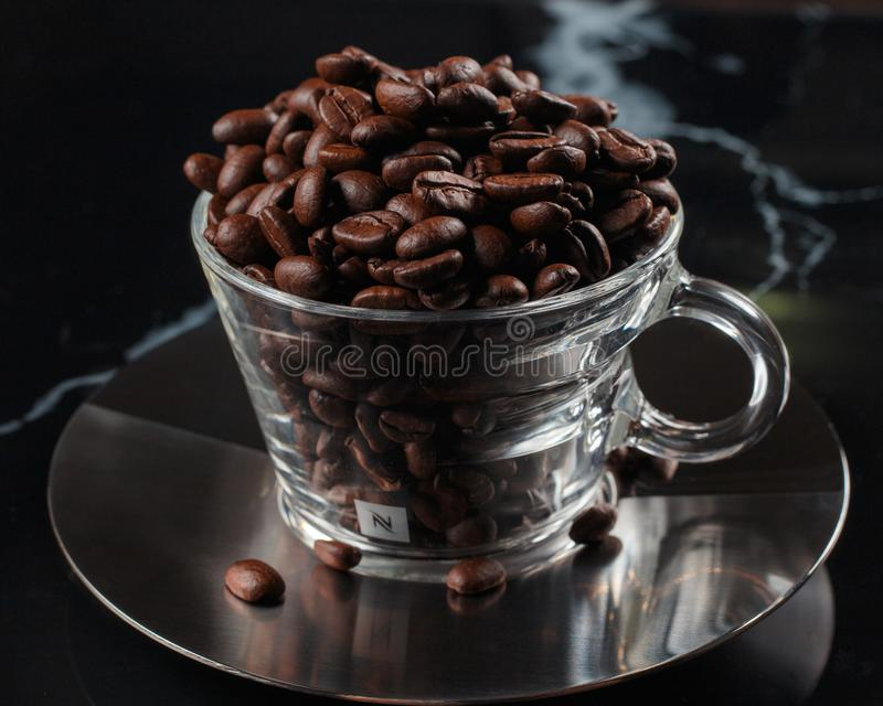 Coffee cup fill up with coffee beans royalty free stock photos