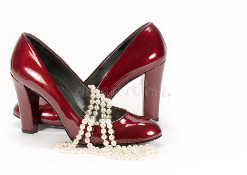 Red Shoes Pearls. Ruby red patent leather high heel shoes draped with strands of pearls on white background stock photos