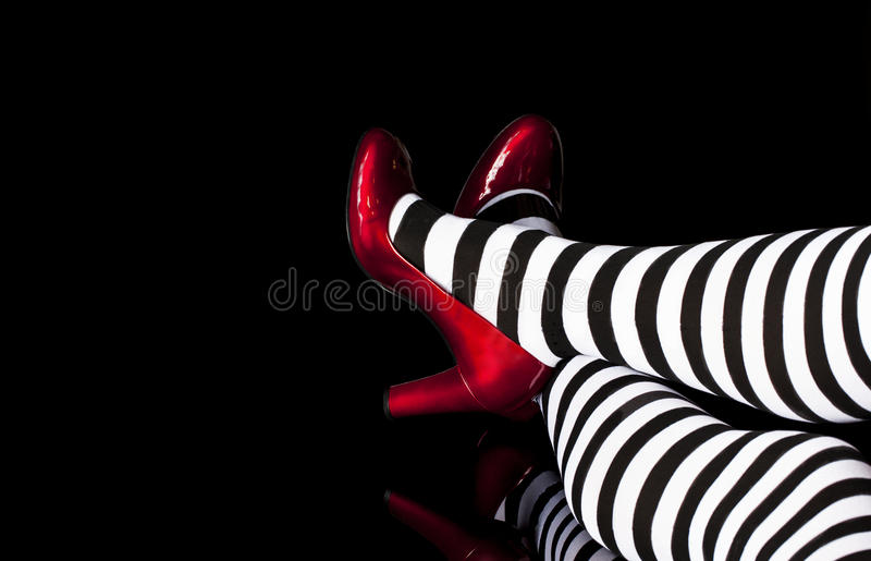 Red Shoes Striped Tights. Legs crossed viewed from knees to shoes, model wearing black and white striped tights and red patent leather high heeled shoes on black royalty free stock image