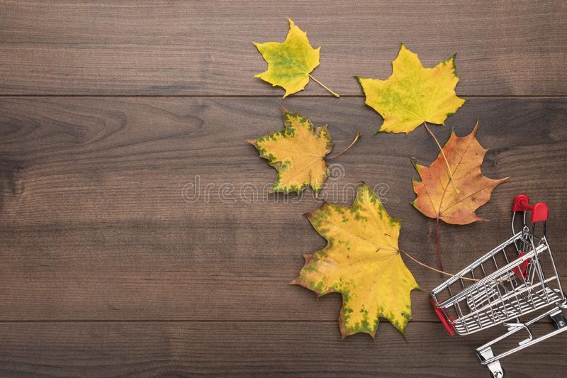 Shopping trolley on wooden background. overturned pushcart and yellow autumn leaves with copy space. fall sale concept stock photos