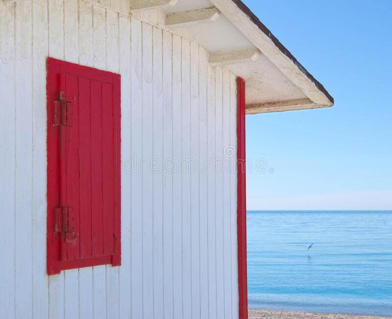 White beach hut with red shutter, blue sea and sky. stock photos