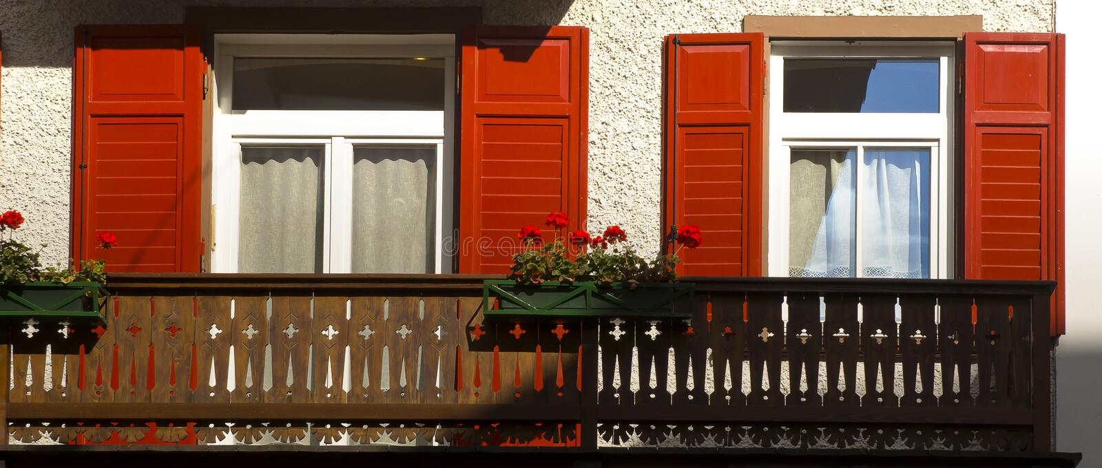 Red shutters flowers, Cortina dAmpezzo, Italy royalty free stock image