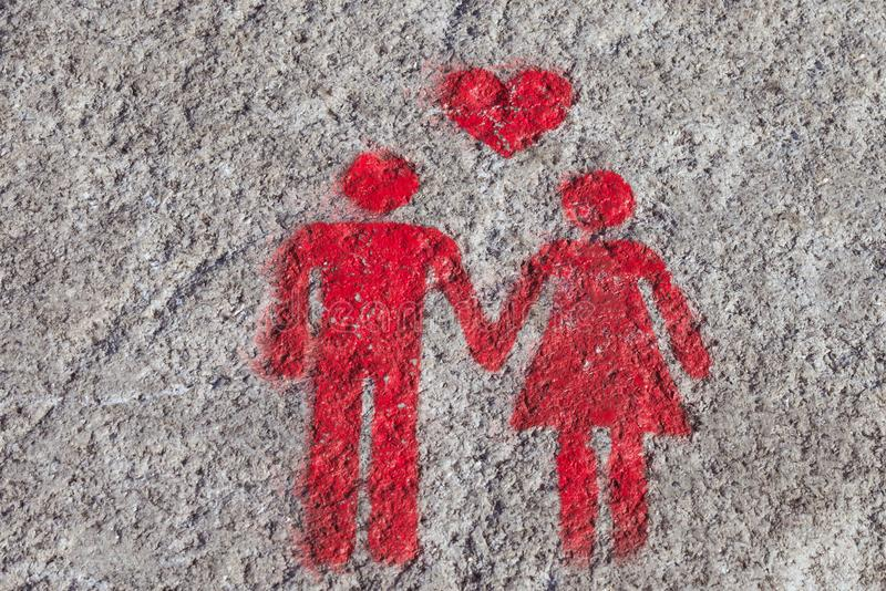 A red sign is drawn on the sidewalk of Porto: the heart, man and woman hold hands. A sign of free space for couples royalty free stock images