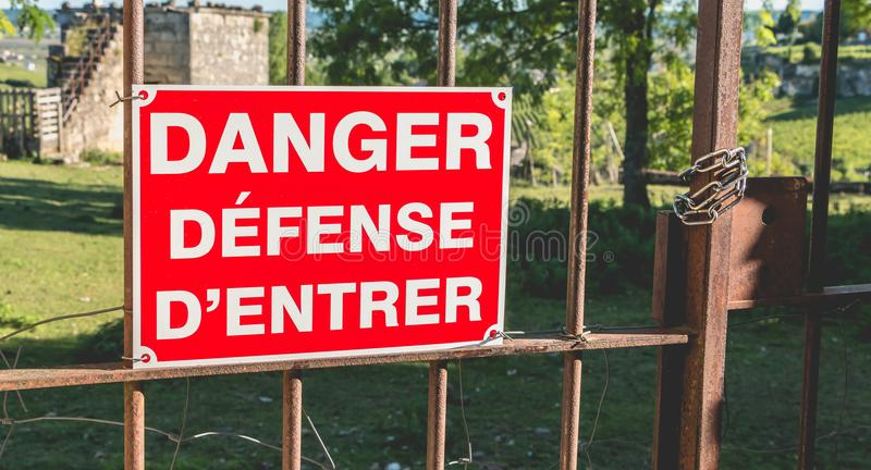 Red sign placed on a rusty gate or it is written in French danger defended to enter. Red sign placed on a rusty gate or it is written in French - danger defended royalty free stock images