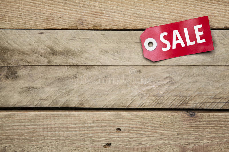 Red sign with Sale on wooden background stock image