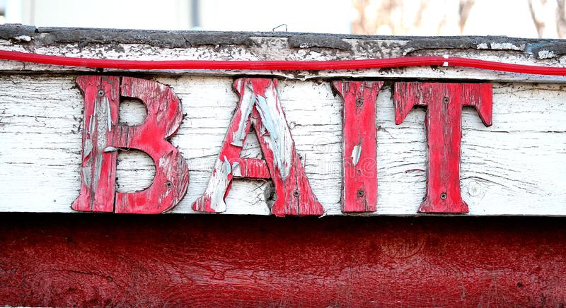 Bait sign for fishing supplies. This is a red sign showing the words bait.  The sign is on the side of a roof line.  The words show a weathered wood look that stock photo