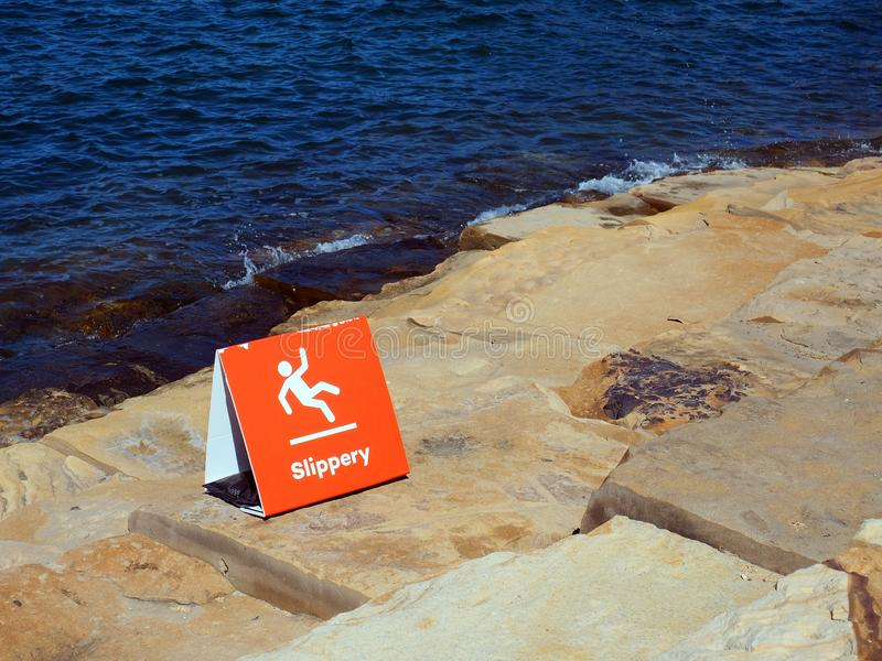 Red Sign Warning of Slippery Rocks stock image