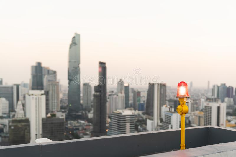 Red signal lamp or aircraft warning light on highrise building or condominium rooftop. Architecture security, safety concept. Red signal lamp or aircraft warning stock image