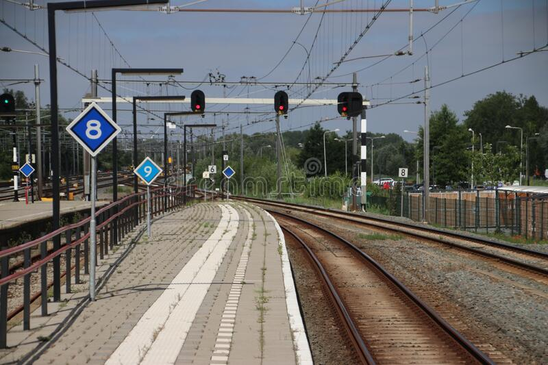 Red signs above railroad tracks heading to Rotterdam at Gouda Railway Station royalty free stock images